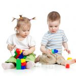 little children playing together with construction set over white background